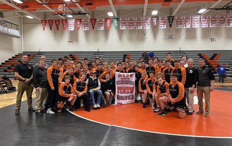 The team smiles with their 2020 state banner after winning both duals.