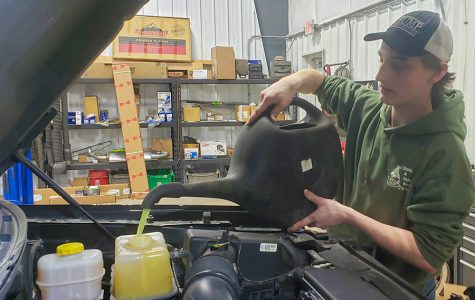 While working at J's Auto, senior Codee Chambers pours antifreeze into a car.