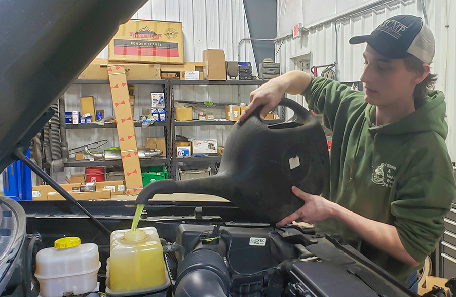 While+working+at+J%27s+Auto%2C+senior+Codee+Chambers+pours+antifreeze+into+a+car.