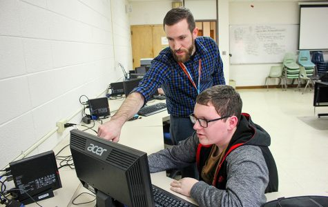 Coach Christian Carper instructs Laiken Blommers (11) at an Esports practice.