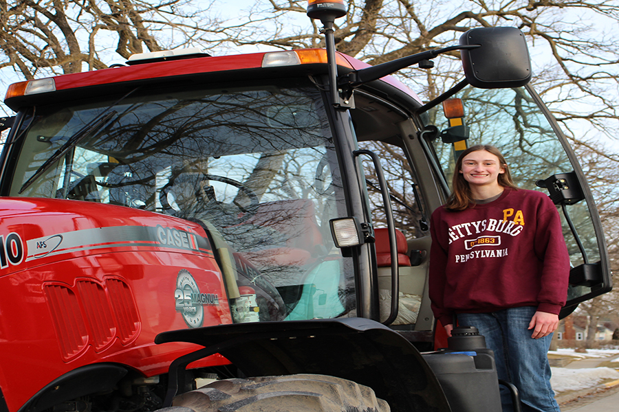 Lori Hilby (10) climbs down from her tractor after driving it to school.