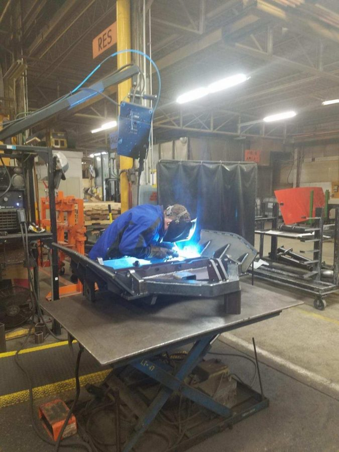 Carter Peyton (11) welds  Dump body parts together in his department.