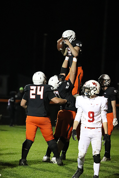 After winning their second playoff game and qualifying for state. Mitch Krogmann (12) throws quarterback Jared Voss (12) into the air.