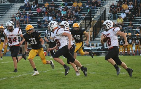 On the Waverly football field, Logan Peyton (10) leads Haze Seibert (9) through the defenders. These two players made up for most of the Hawks' rushing yards.