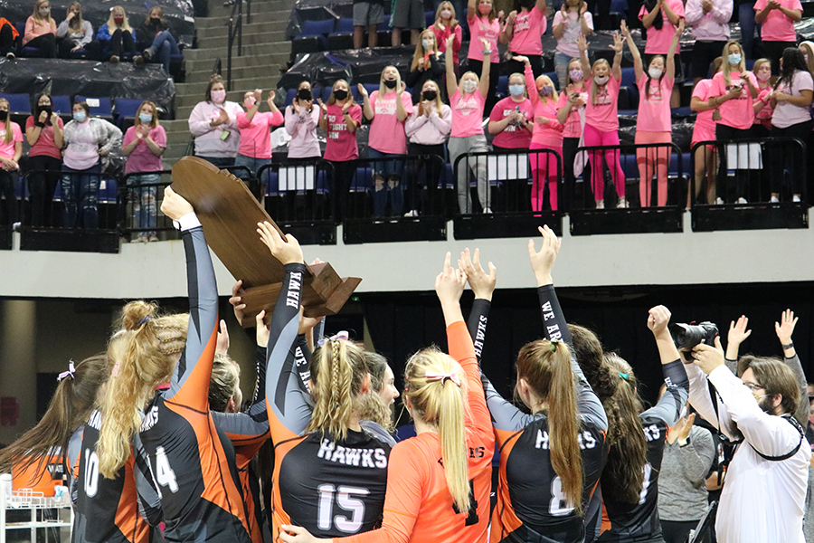 After the championship game at the Alliant Energy Powerhouse, the volleyball girls hold their trophy while the student section cheers them on.