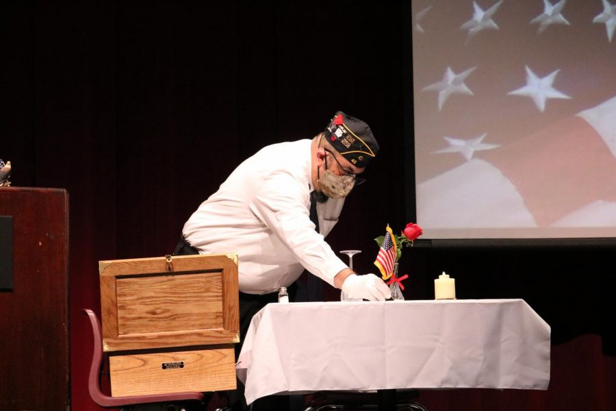A Veteran from the American Legion Club sets the table for POW and MIA soldiers.
