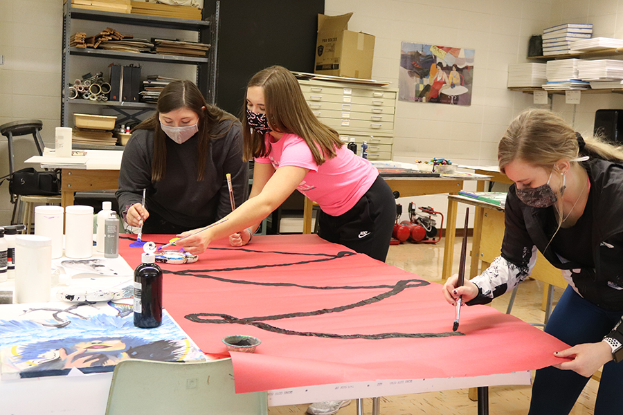 Decorating their door for the holidays, Hallie Wenger (12), Anna Werner (12) and Karsyn Welcher (12) paint Christmas lights onto a sheet of paper for their door.