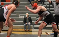 Attempting to lock up with his opponent, senior Cael Meyer reaches at Western Dubuque wrestler.