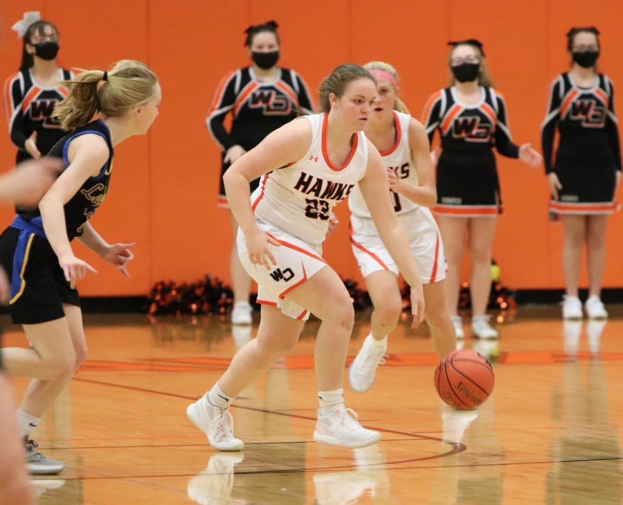 Senior Mia Peyton dribbles the ball down the court at a home basketball game.