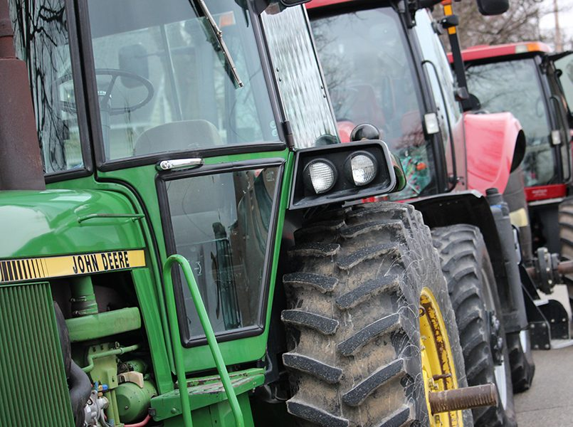 A John Deere tractor and two Case IH tractors park on the west side of New Street.