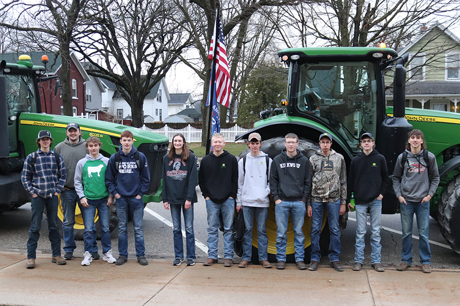 On Tractor Day, Noah Jackson (11), Mitch Krogmann (12), Kaden Ryan (10), John Beswick (9), Lori Hilby (11), Phillip Ries (11), Blake Deutmeyer (11), Andrew Ries (11), Kyle Deutmeyer (12), Trent Deutmeyer (10) and Landon Rausch (10) pose in front of Ryan and  Krogmann's tractors.