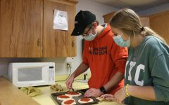 Lukas Meyer and Kylinne Meyers spread pizza sauce on the dough and add the toppings.