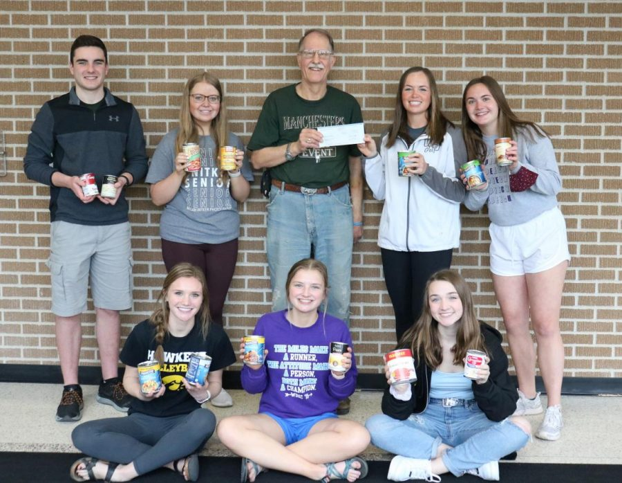 West Delaware Student Council donates canned food and a check to Doug Robbins of the Delaware County Food Pantry.  Front Row: Maddie Hoeger, Makayla Gasper, Isabella Kenellis; Back Row: Jacob Wenger, Natalie Kehrli, Doug Robbins, Morgan Collier, Anna Werner.