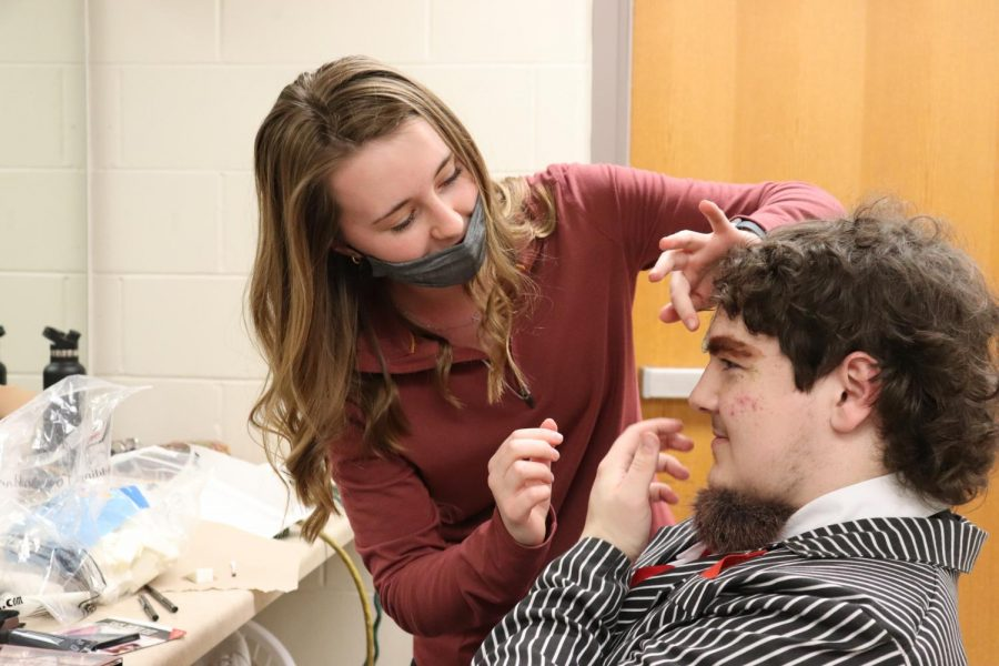 Before the show, senior Katie McGrane does junior Aiden Lee's makeup for his role of the wolf.