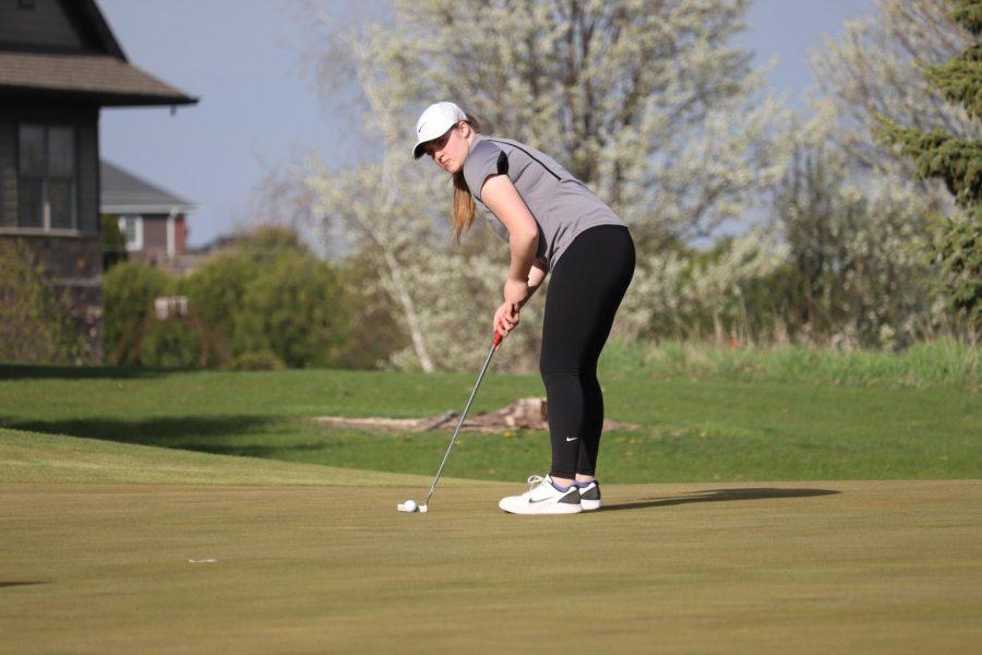 On April 26, Mia Peyton prepares to chip the green.