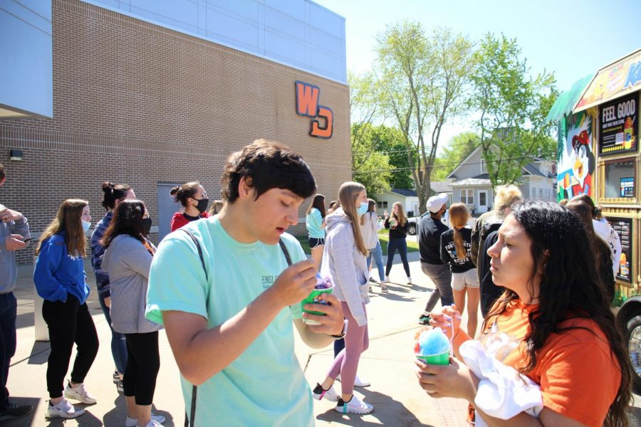 Brayden Moulds (12) and Carla Gomez (12) eat shaved ice outside during lunch on senior service day