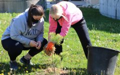 Hallie Wenger (12) and Jadyn Werner (12) plant trees at the water treatment plant.