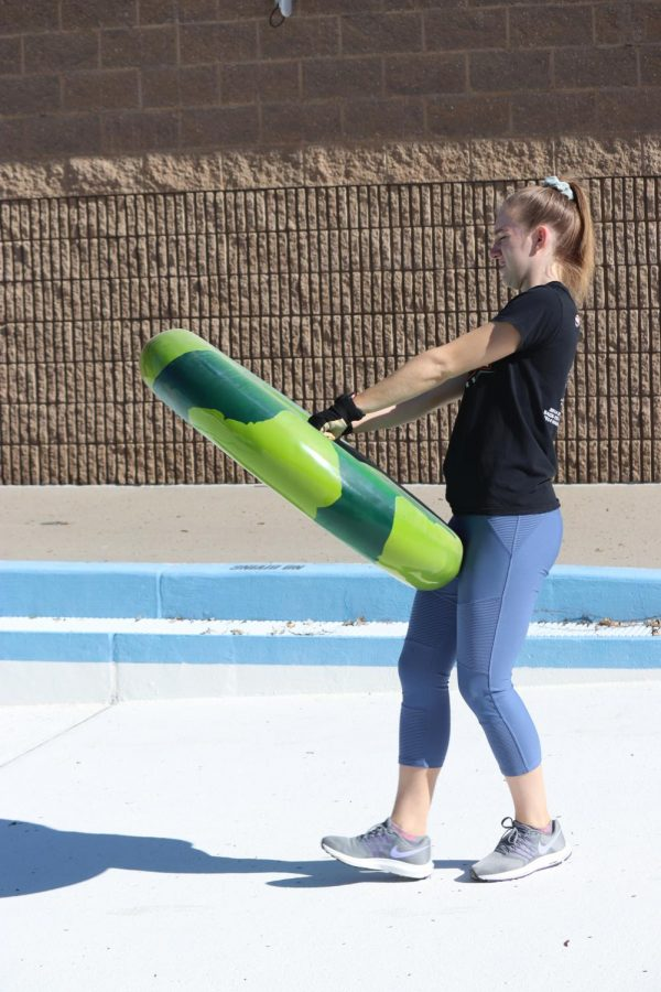 Addison Reetz (12) assists in cleaning the pool at the Aquatic Center.