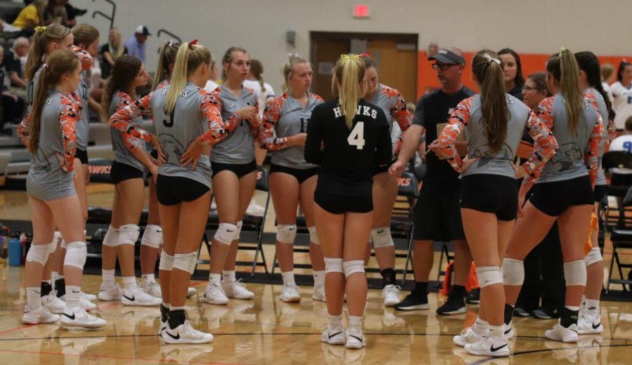 Coach Brett Mather gives the volleyball girls  strategy before a match during the Thursday night season opener.