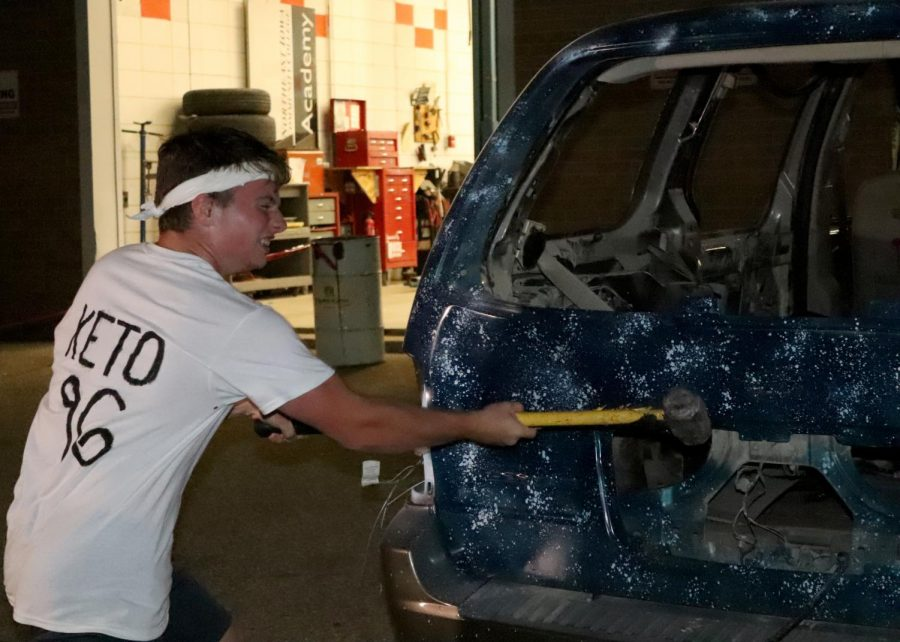 In the auto's parking lot, Zachariah O'Rear (11) helps to demolish a car during the Car Bash on Sept. 30. All students made a free-will donation to participate.