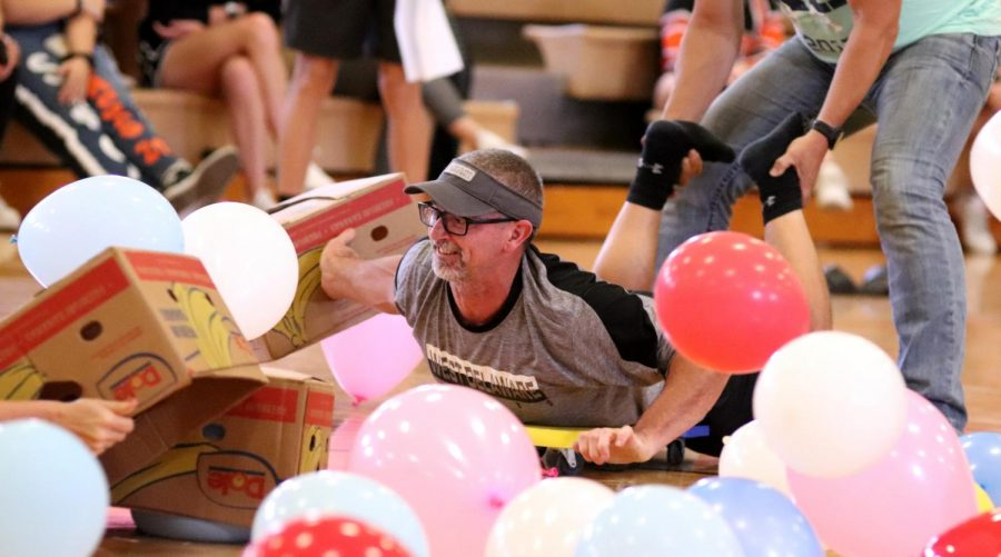 Participating in the Homecoming Olympics, Bret Mather, teacher and renowned volleyball coach, reaches to catch balloons during the Hungry Hungry Hippos game. Mather was representing the junior class. We lost, Mather said. All I wanted [after we lost] was another chance at it. Teacher Jennie Voss won the game for the senior class.